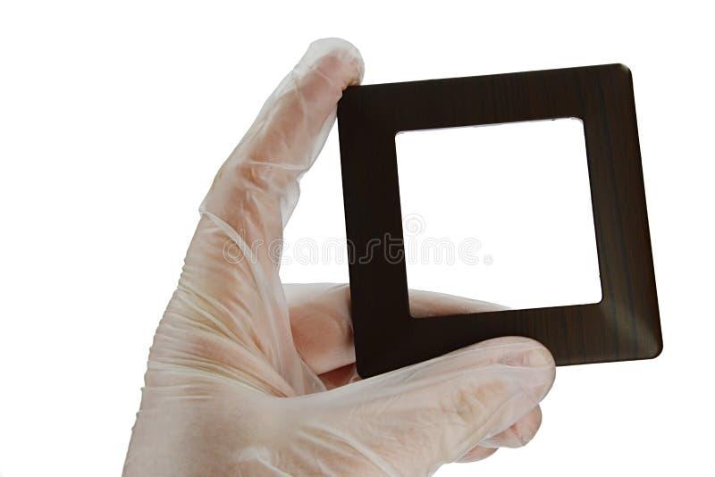 木设计塑料灯开关框架,木仿制表面在左手的手指举行了在透明乳汁安全手套, w的 图库摄影