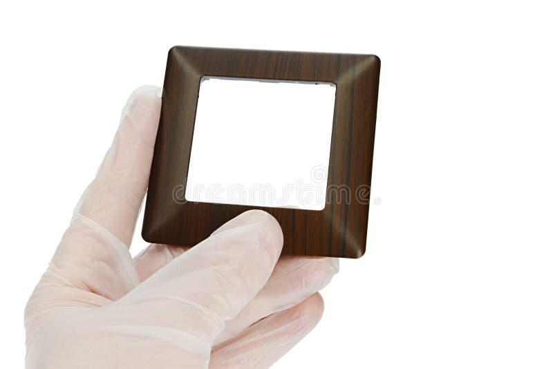 木设计塑料灯开关框架,木仿制表面在左手的手指举行了在透明乳汁手套的 库存照片
