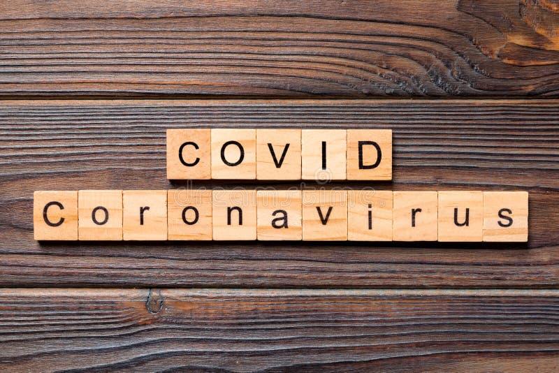 木质背景上铭记COVID冠状病毒 在木块上写的可视字 在木制桌子上发文供您设计,武汉 免版税库存照片