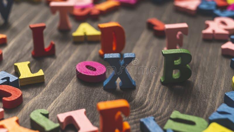 木质背景中的彩色木字 免版税库存图片