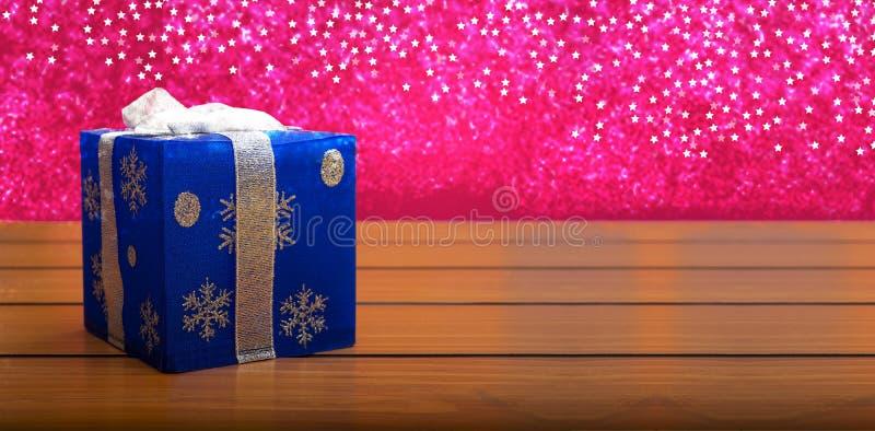木质背景为雪的蓝色圣诞礼盒,复制空间横幅 免版税库存图片