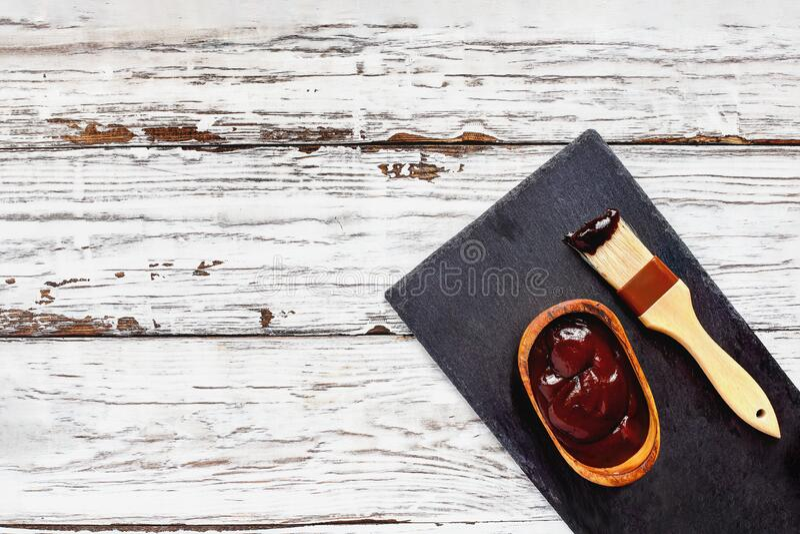 木质背景刷碗中的烧烤酱 免版税库存图片