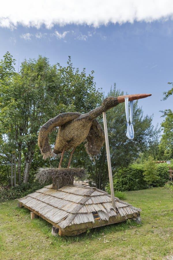 木起重机在奥地利阿尔卑斯带来婴孩雕象 库存图片