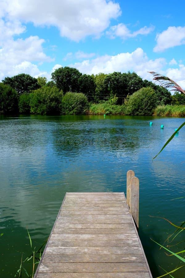 木跳船,突出入有树的一个镇静游泳湖我 库存照片