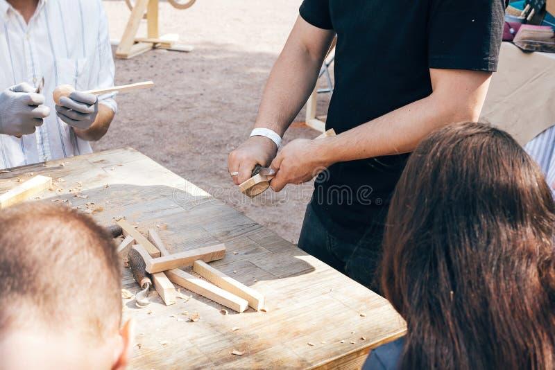 木车间 雕刻从木头的手匙子,与凿子关闭一起使用 做木匙子、凿子和削片的过程 免版税库存图片