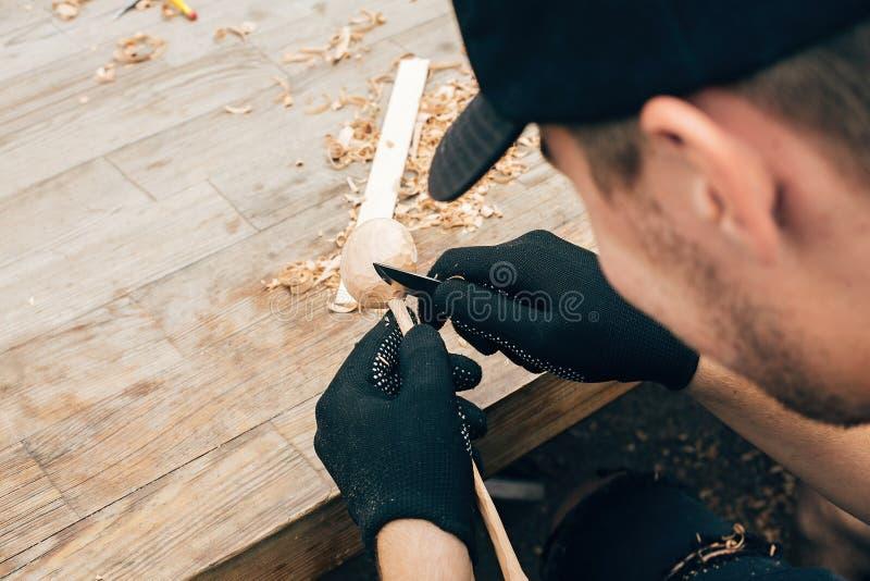 木车间 雕刻从木头的手匙子,与凿子关闭一起使用 做木匙子的过程,凿子,铅笔, 免版税库存照片