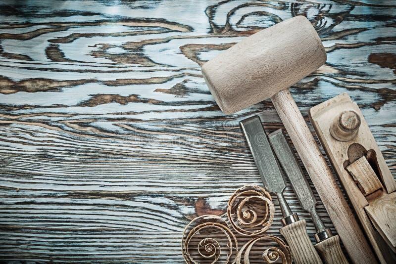 木锤子凿在木委员会的更加平面的计划芯片 免版税图库摄影