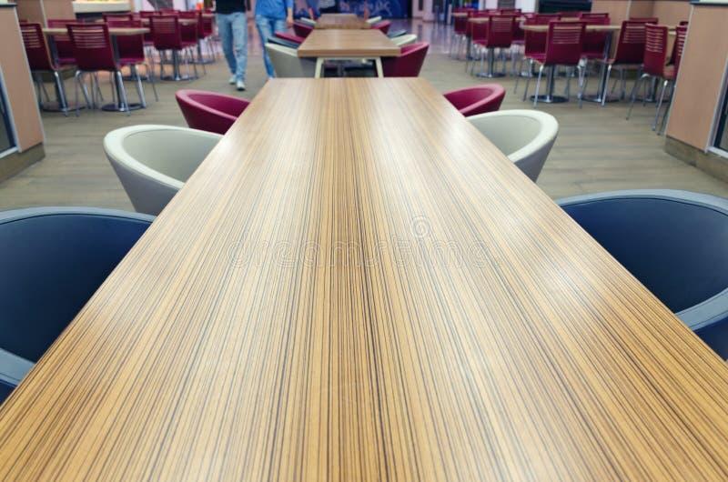 木长的黄褐色桌顶视图与蓝色和白色椅子的 咖啡馆内部细节在购物中心 库存图片