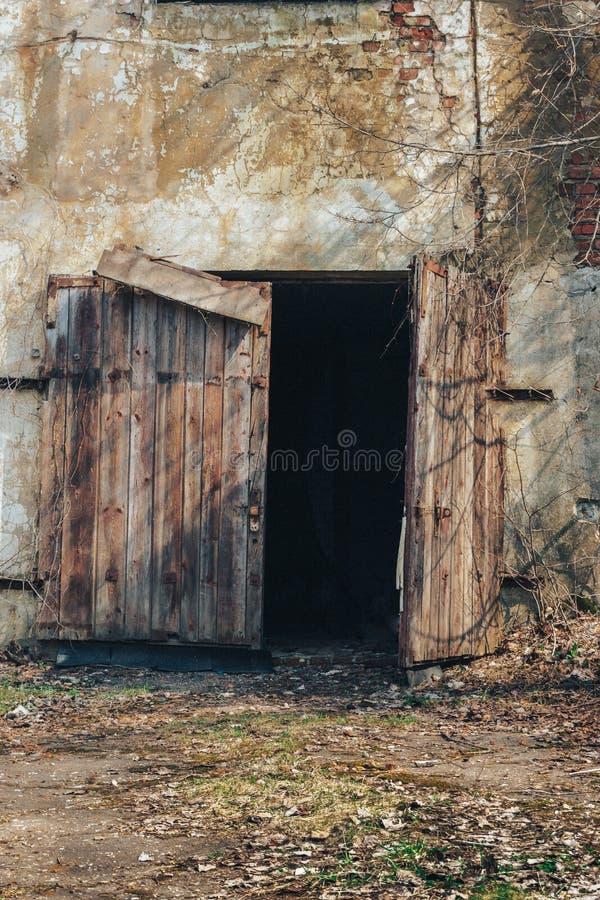 木门在老被放弃的工厂仓库里崩溃了 免版税库存照片
