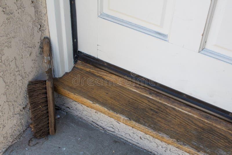 木门限、门和一个家的具体着陆有一把老鞋子刷子的在角落 免版税库存图片