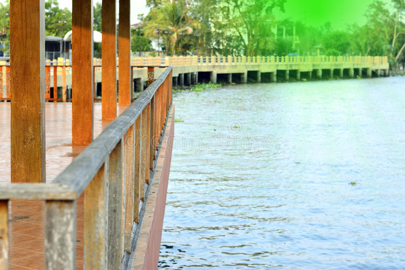 木阳台或木大阳台在河附近有阳光的 免版税库存照片