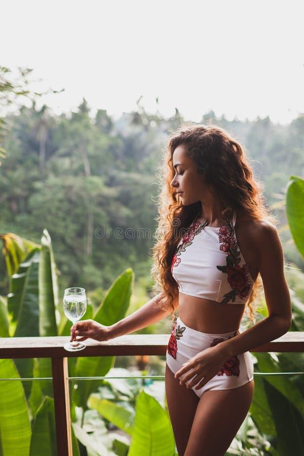 木阳台的妇女有热带密林视图 库存照片