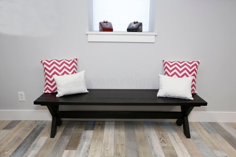 木难倒的长木凳和枕头对此在窗口附近 免版税图库摄影