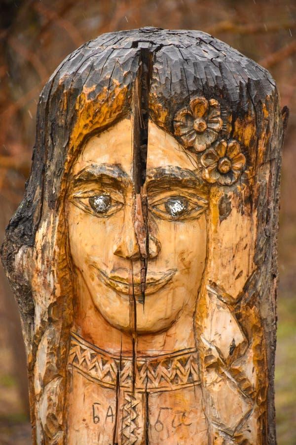 木雕塑在以妇女的面孔的形式公园 库存照片