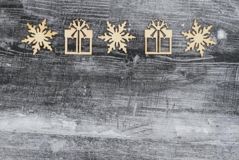 木雪花和圣诞礼物在被风化的木背景 免版税库存图片