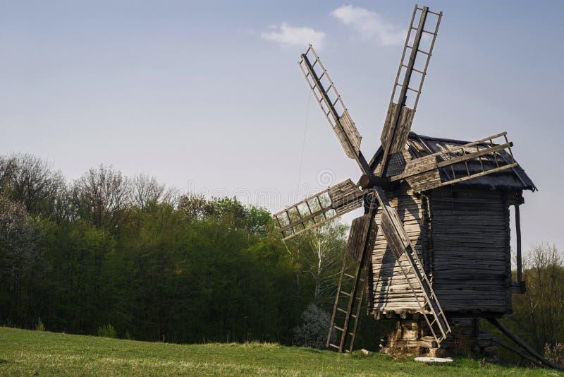 木风车和磨石在山坡反对森林和天空蔚蓝背景  库存图片
