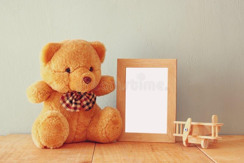 木飞机玩具和玩具熊在木桌在空白的照片框架旁边 减速火箭的被过滤的图象 准备安置摄影 免版税库存照片