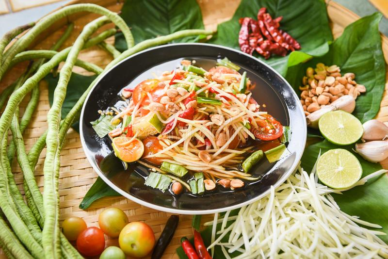 木餐桌上供应木瓜沙拉-盘上的青木瓜沙拉辣泰国菜,配以粗豆草和香料 免版税图库摄影