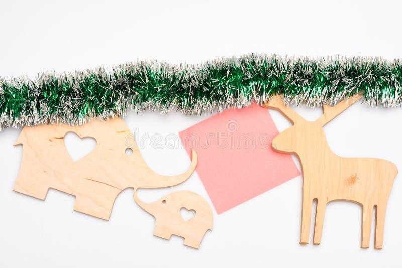 木鹿和大象玩具或者装饰与纸笔记的关于白色背景 装饰圣诞节假日 免版税库存照片