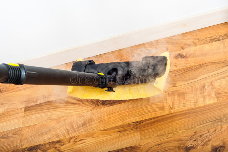 木,木条地板,清洗与蒸汽的层压制品的地板在屋子里 免版税库存图片