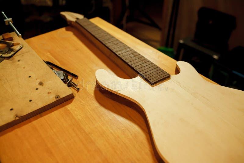 木头宿营低音吉他的 制造和修理乐器 库存照片