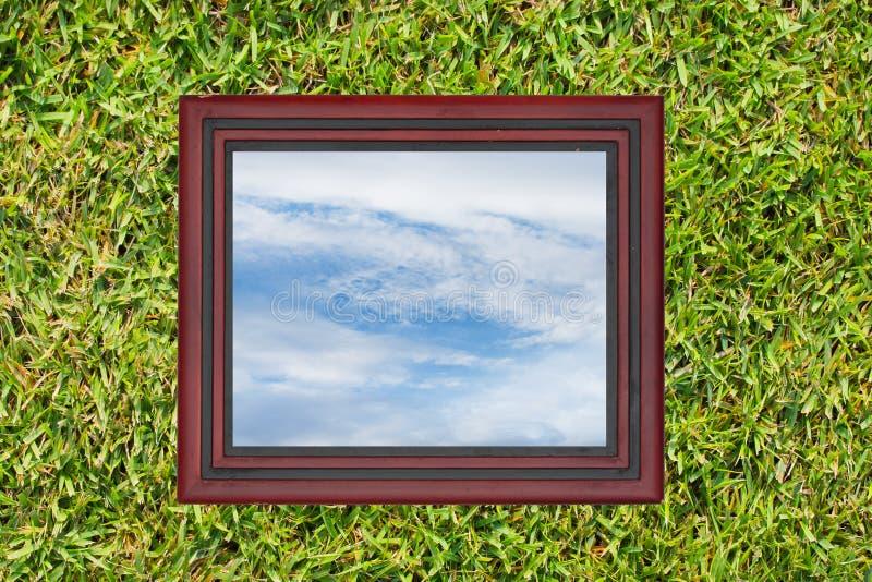 木画框有天空看法,在绿草墙壁backg 库存照片
