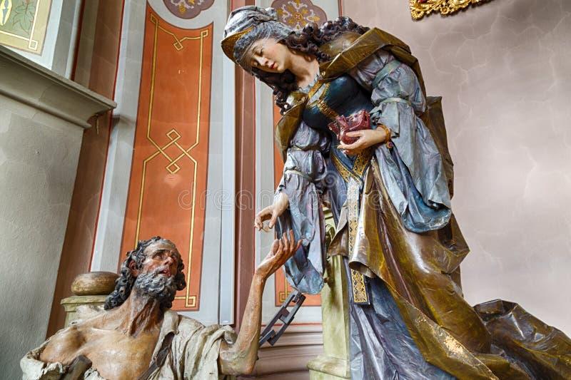 木头雕刻了圣徒伊丽莎白雕象有叫化子的慈善的g 库存照片