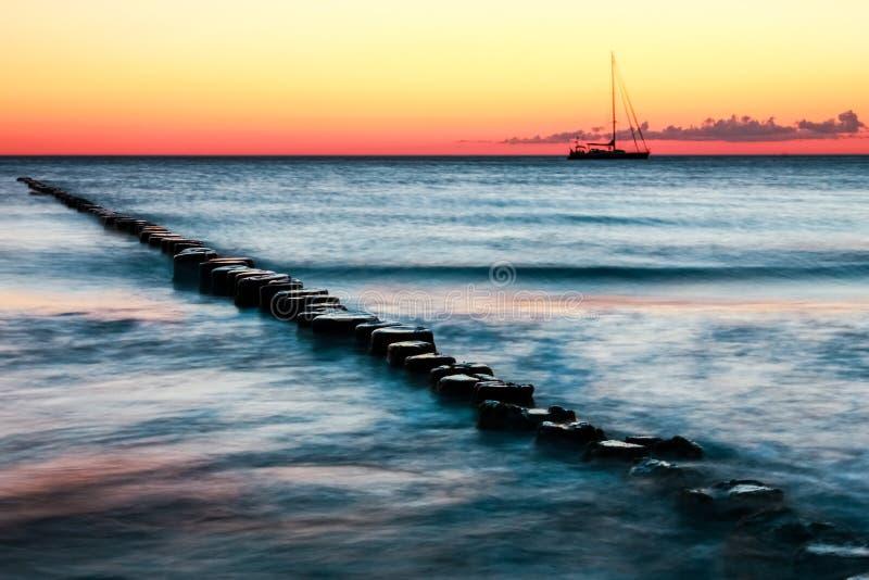 木groynes和帆船 红色日落和长的曝光 库存图片