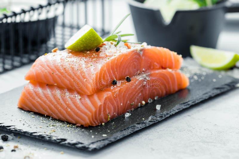 未加工的三文鱼内圆角两个片断用新鲜的草本迷迭香、香料和橄榄油在黑板岩板材 库存图片