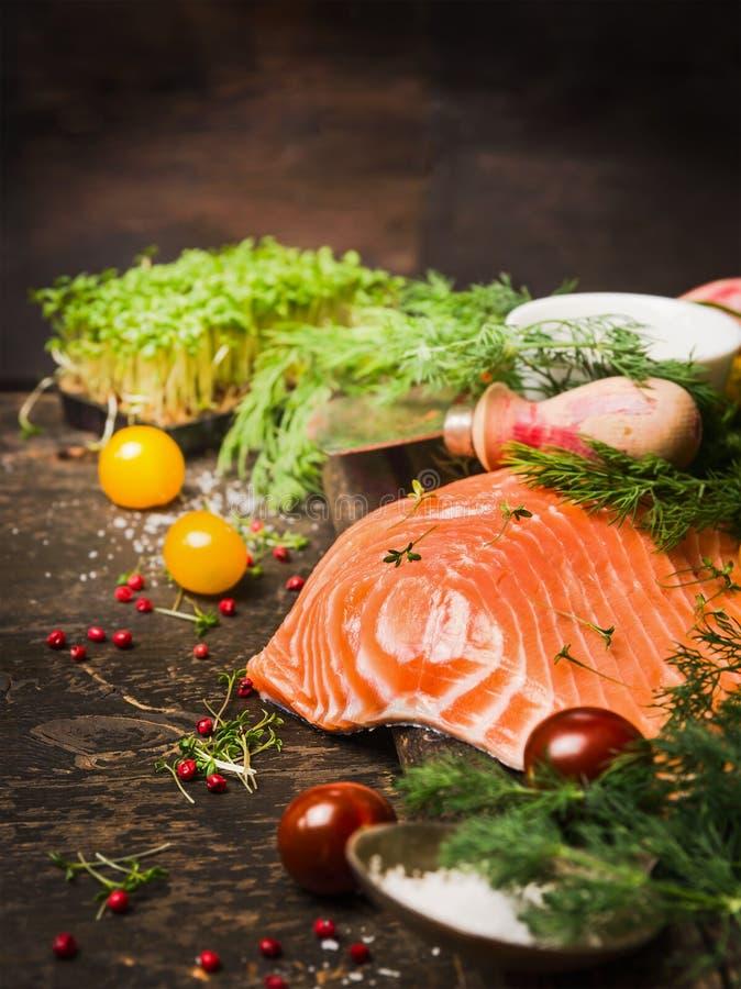 未加工的三文鱼内圆角用新鲜的草本和蕃茄在土气木背景 免版税库存照片