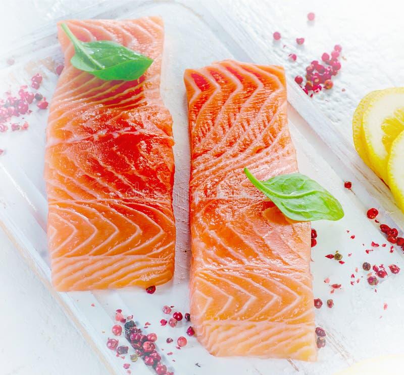 未加工的三文鱼内圆角用草本、香料和柠檬 免版税图库摄影