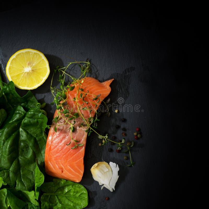 未加工的三文鱼内圆角用麝香草、大蒜、柠檬和菠菜在dar 免版税库存图片