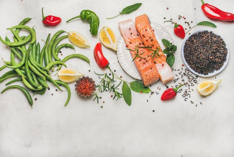 未加工的三文鱼鱼片牛排平位置与菜的,绿色 免版税库存图片