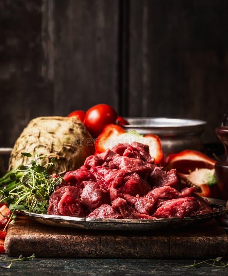 未加工的切成小方块的牛肉肉和有机菜成份炖煮的食物或墩牛肉烹调的 在年迈的厨房用桌上的食物配制 库存图片