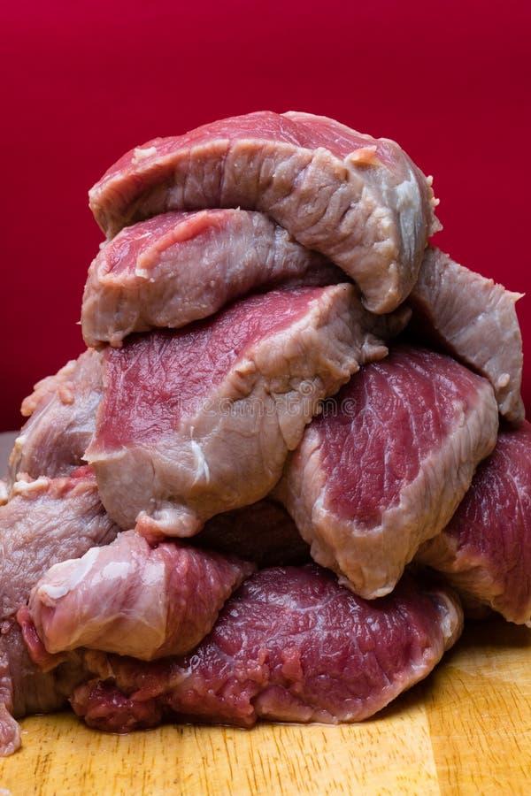 未加工的切成小方块的牛肉肉片断富蛋白质,在红色背景 库存图片