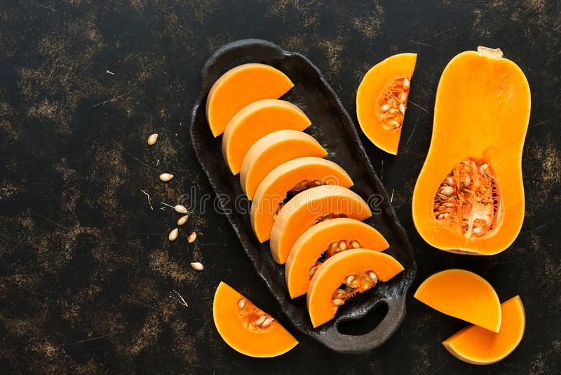未加工的南瓜片断在黑陶器的 顶视图,拷贝空间 秋天的概念 万圣节 图库摄影