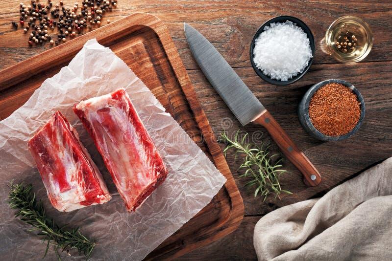 未加工的在白色烹调纸和木切开的桌的小牛牛排骨 免版税库存图片