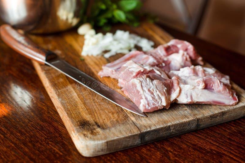 未加工的新羊羔肉肋骨和调味料在木背景 免版税库存图片