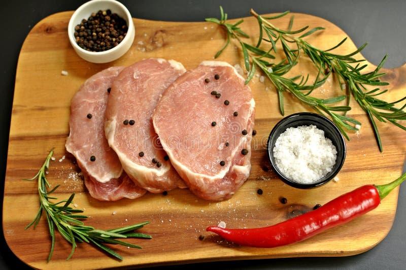 未加工的新鲜的未煮过的被切的猪肉内圆角盘用迷迭香、胡椒、盐、红辣椒和大蒜在木板和黑色 图库摄影