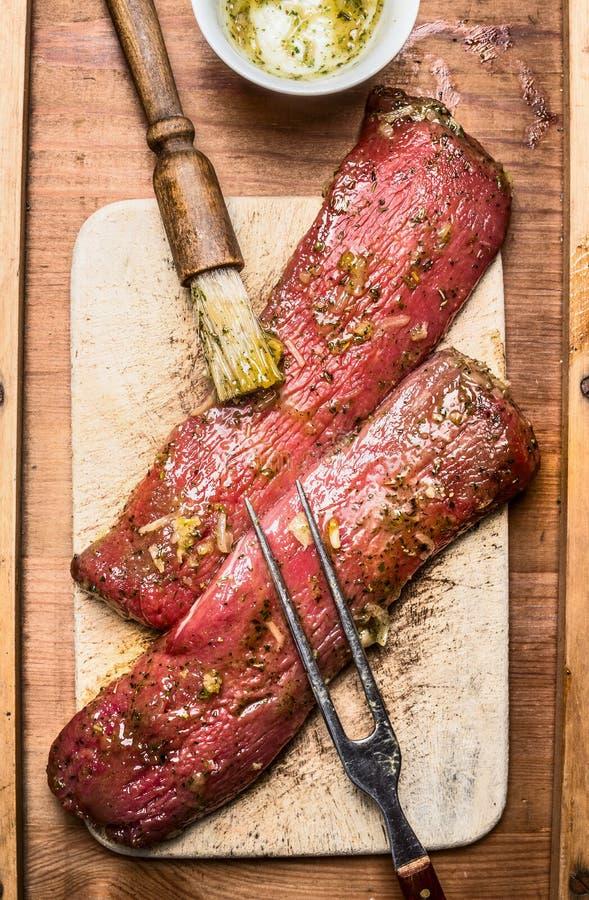 未加工的新鲜的羊羔内圆角用卤汁泡为烹调的或与刷子和肉的BBQ格栅分叉,顶视图 库存照片