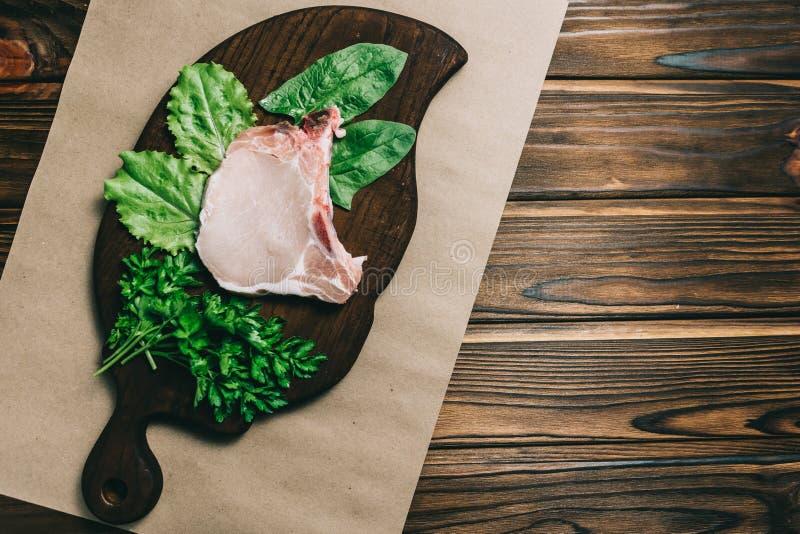 未加工的新鲜的肉猪肉牛排和seasRaw新鲜的肉猪肉牛排和调味料在aonings在一个黑暗的木背景板用蜂蜜 免版税库存图片