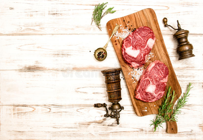 未加工的新鲜的肉Ribeye牛排 海湾小豆蔻大蒜草本叶子胡椒迷迭香盐加香料香草 背景许多饺子的食物非常肉 免版税库存图片