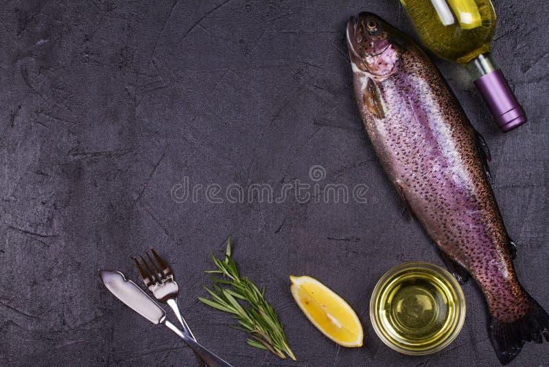 未加工的新鲜的鳟鱼、白葡萄酒瓶、柠檬和草本在灰色石纹理背景 看法从上面,顶面演播室射击 库存照片