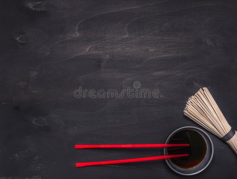 未加工的日本荞麦面条用酱油和红色筷子地方文本的,构筑木土气背景顶视图 免版税库存照片