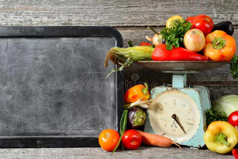 未加工的有机新鲜蔬菜的构成,文本的,在木棕色桌上的平衡粉笔板 免版税库存图片