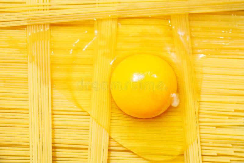 未加工的未煮过的意大利面团tagliatelle与,面团切削刀、碗用白面和残破的鸡蛋 与空间的顶视图文本的 免版税库存照片