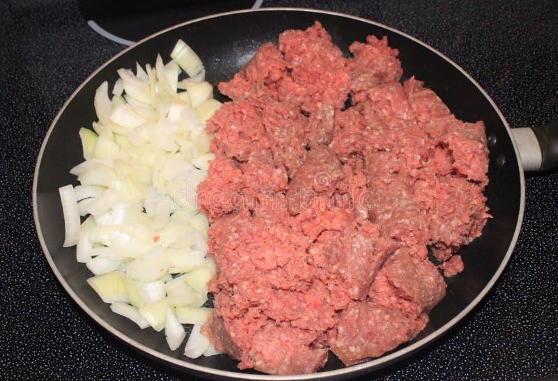 未加工的汉堡包和葱在煎锅 图库摄影