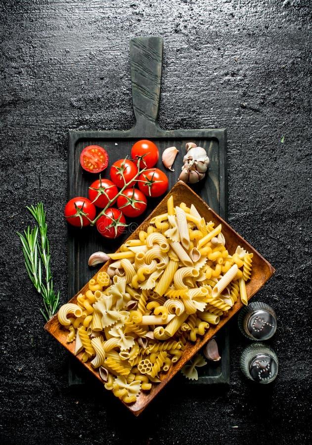 未加工的浆糊不同形式在一块板材的用蕃茄、大蒜和迷迭香 免版税库存图片