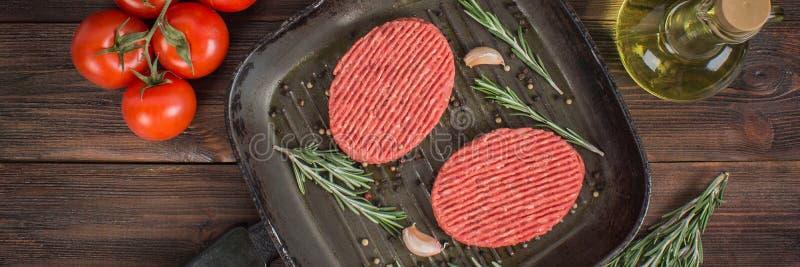未加工的炸肉排平底锅用迷迭香和大蒜 木棕色backgroun 免版税库存图片