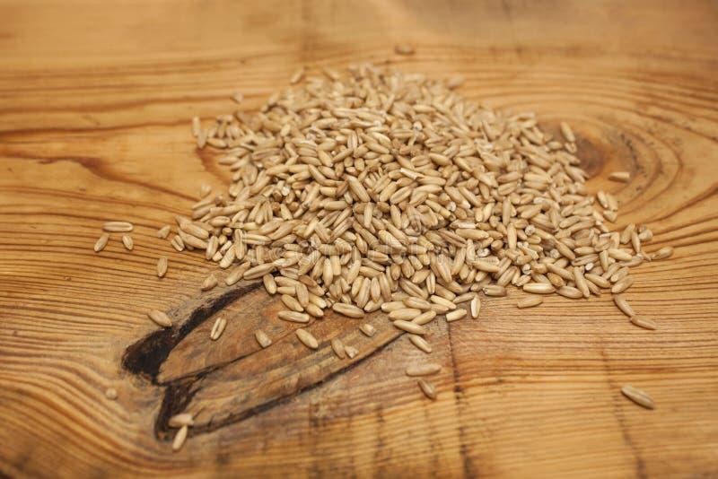 未加工的燕麦五谷,低热值成份在木背景的可口健康早餐,拷贝空间 库存照片